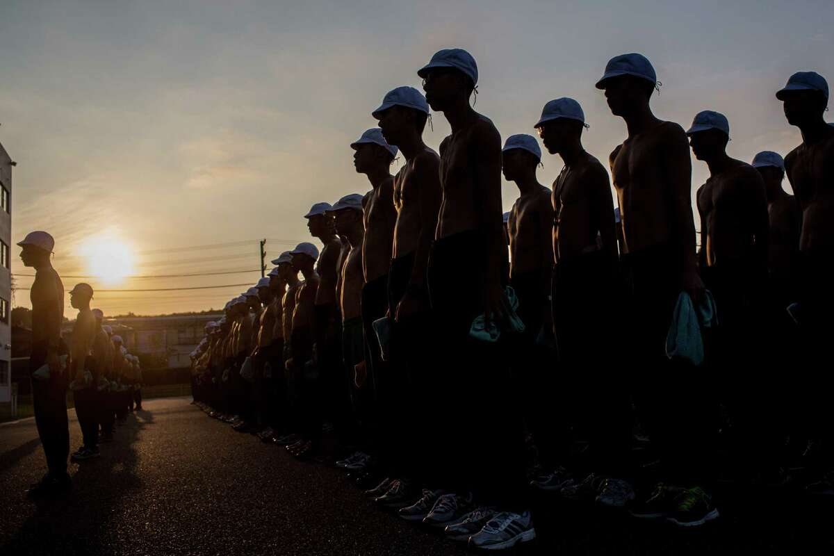 First grade students assemble at first light to receive the days training schedule at the Japan Ground Self-Defense Force (JGSDF) High Technical School on September 17, 2014 in Yokosuka, Japan.