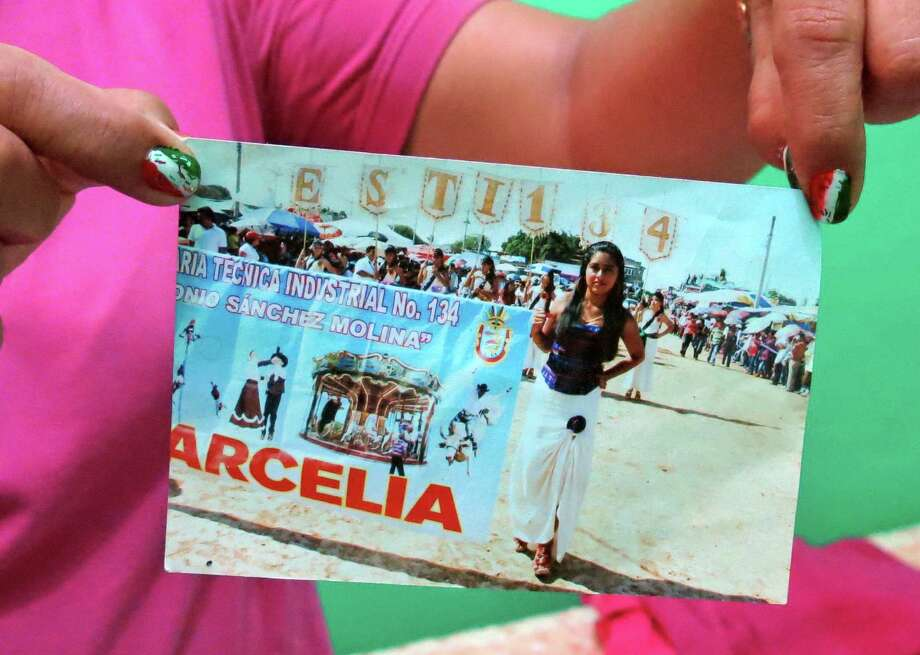 A woman who didn't want to give her name for fear of reprisals holds a photograph of her 15-year-old daughter, whose death she witnessed. Photo: Eduardo Castillo / Associated Press / AP