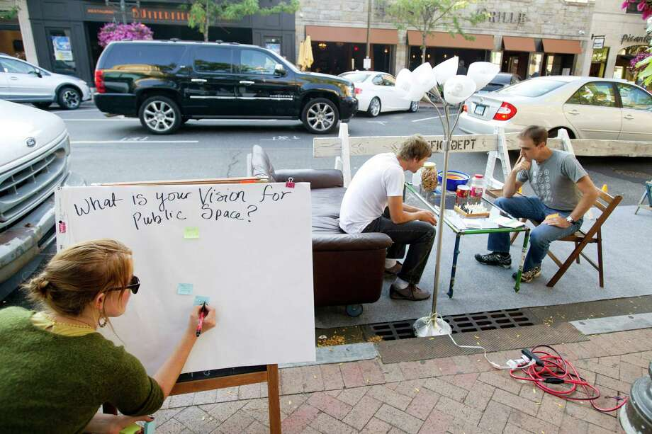 Emily Provonsha, left, makes a poster asking passers-by for their opinions as Andrew Pezzimenti, center, and Mike Norris, right, play chess at a parklet in front of Lorca on Bedford Street in Stamford, Conn., on Friday, September 19, 2014. The parklet it set up in a parking space and is intended to encourage people to think about how best to use public space. Photo: Lindsay Perry / Stamford Advocate