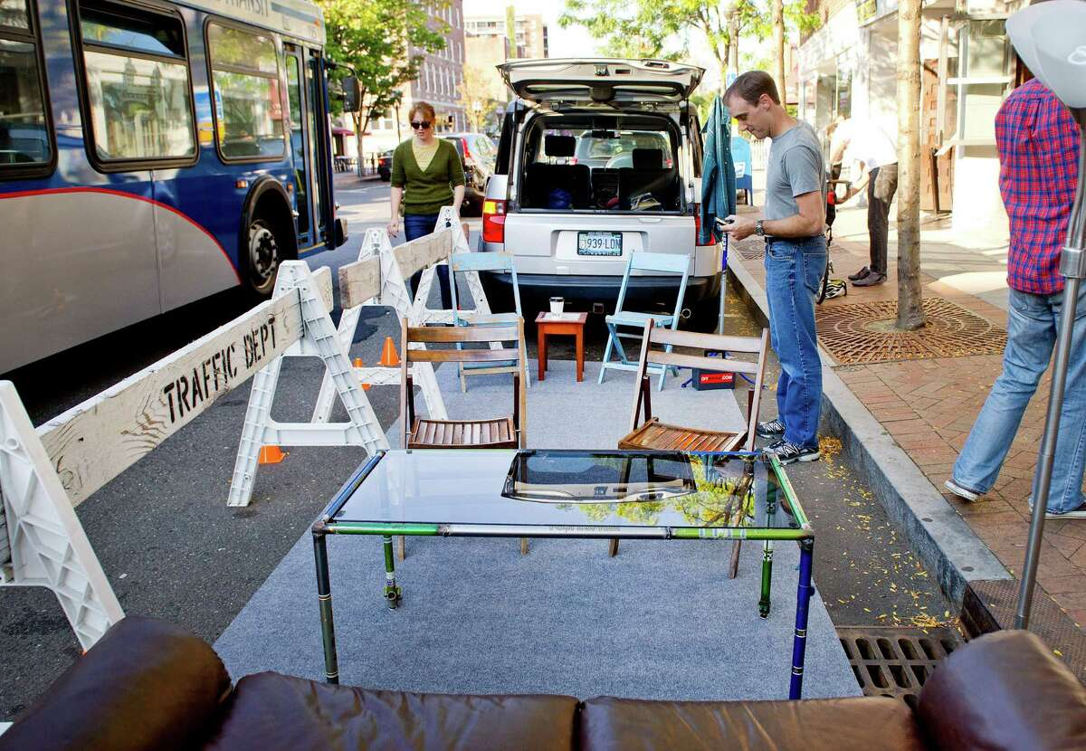 Mike Norris, right, and Emily Provonsha, left, help set up a parklet in front of Lorca on Bedford Street in Stamford, Conn., on Friday, September 19, 2014. The parklet it set up in a parking space and is intended to encourage people to think about how best to use public space.