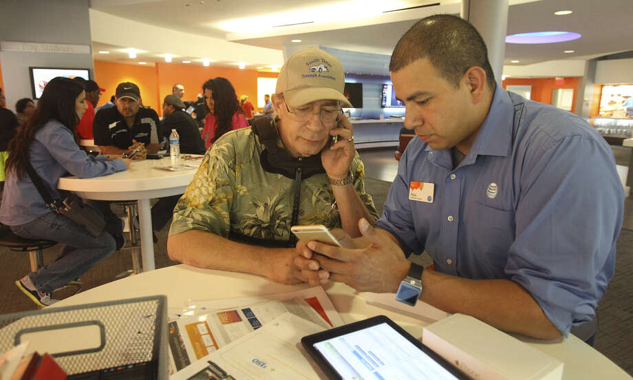 Steve Gold (center) buys his new iPhone 6 Plus at the AT&T store in the 13000 block of U.S. 281 North. Gold says he has been first in line at that store for new iPhone releases over the past five years. Helping Gold is employee Felix Ramos. Photo: Photos By John Davenport / San Antonio Express-News / ©San Antonio Express-News/John Davenport