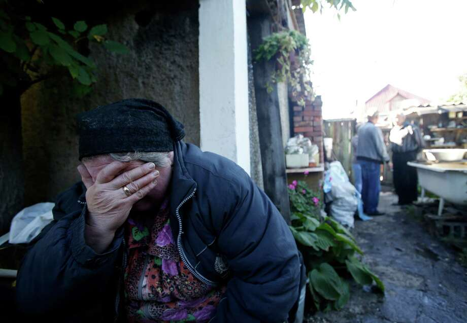 Local resident Luba Zikova cries in front of her damaged house after shelling in the town of Donetsk, eastern Ukraine, Friday, Sept. 19, 2014. One person was killed by overnight shelling in a neighborhood in the north of the city, where fighting centered around the government-held airport has spilled over into residential areas.(AP Photo/Darko Vojinovic) Photo: Darko Vojinovic, STF / AP