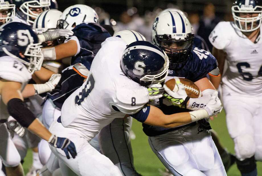 Wilton's TJ Savvaides carries the ball as he is tackled by Staples' Evan Gilland during Friday's football game at Wilton High School on September 19, 2014. Photo: Lindsay Perry / Stamford Advocate