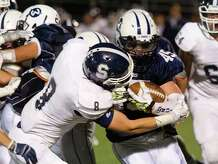 Wilton's TJ Savvaides carries the ball as he is tackled by Staples' Evan Gilland during Friday's football game at Wilton High School on September 19, 2014.