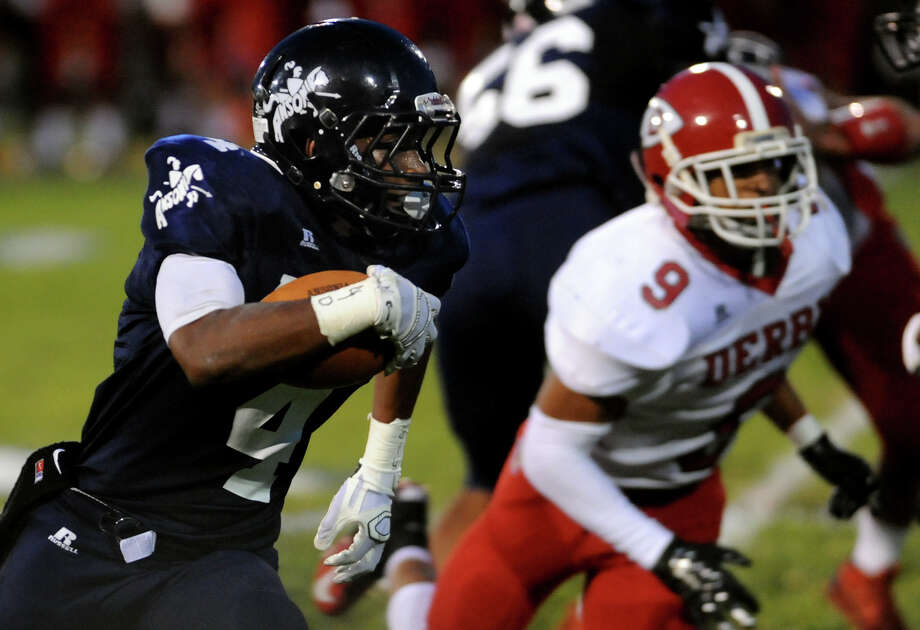 Ansonia's Tajik Bagley carries the ball over forty yards in the play for a touchdown, during high school football action against Derby in Ansonia, Conn., on Friday Sept. 19, 2014. Photo: Christian Abraham / Connecticut Post