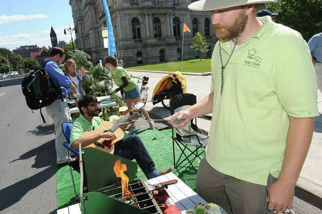 Drew Pollak-Bruce, right, with Parks & Trails New York roasts a marshmallow as part of Park(ing) Day in paid a parking spot on Washington Avenue on Friday Sept. 19, 2014 in Albany, N.Y.  (Michael P. Farrell/Times Union) Photo: Michael P. Farrell / 00028661A