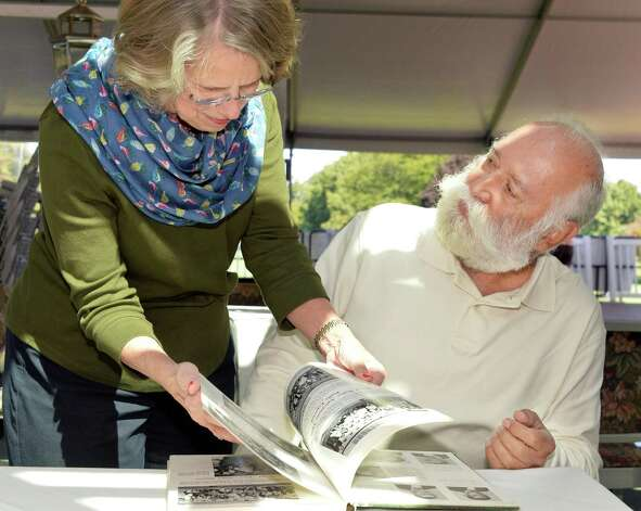 Onetime classmates, Cindy Bard Ball, left, of Niskayuna,, and Alvaro Nino Guerrero, right, of Colombia, a foreign exchange student in 1964, reminisce over an old yearbook  as they prepare for the Niskayuna High School Class of 1964's reunion this weekend at the Mohawk Country Club Friday Sept. 19, 2014, in Niskayuna, NY.  (John Carl D'Annibale / Times Union) Photo: John Carl D'Annibale / 00028700A