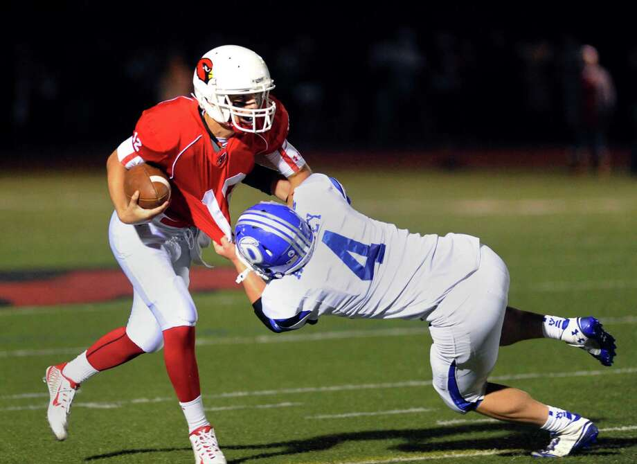 At right, Darien's Peter Archey (#4) sacks Greenwich quarterback Matt Marzulla (#12) during the high school football game between Darien High School and Greenwich High School at Greenwich, Friday night, Sept. 19, 2014. Darien defeated Greenwich, 33-26. Photo: Bob Luckey / Greenwich Time