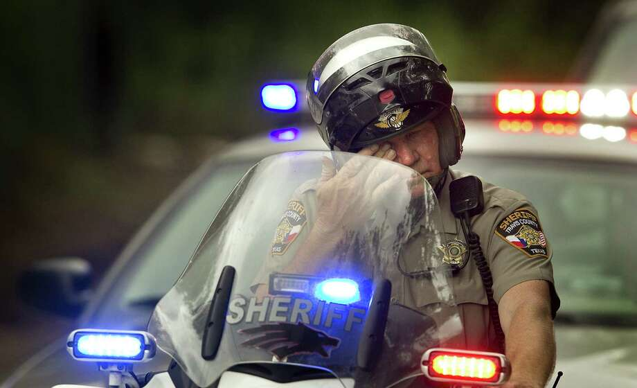 A member of the Travis County Sheriff's department wipes his eye after he and others formed a procession to escort the body of Deputy Jessica Hollis. Photo: Laura Skelding / Associated Press / Austin American-Statesman