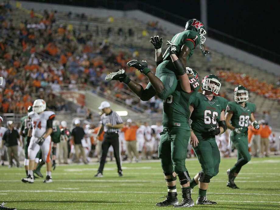 The Woodlands offensive lineman Connor Mackie (55) celebrates by picking up Patrick Carr after he rushed 11 yards for his third touchdown of the night in the Highlanders' 49-3 victory over La Porte. Photo: Thomas B. Shea, Freelance / © 2014 Thomas B. Shea