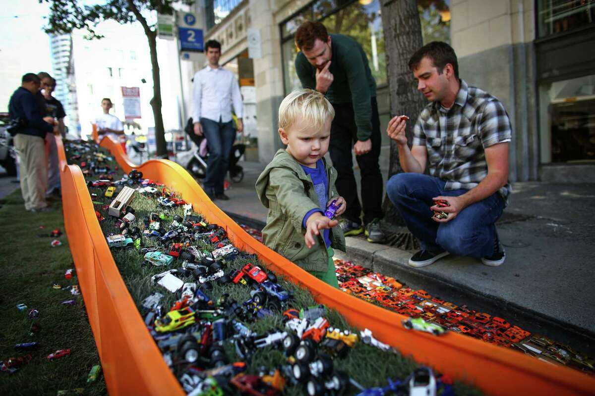Hunter Merrill, 2, pushes a Hotwheels toy car along a track created by Bohlin Cywinski Jackson architects during PARK(ing) Day on Friday, September 19, 2014. PARK(ing) Day is an annual event that transforms parking spaces in to active community spaces.