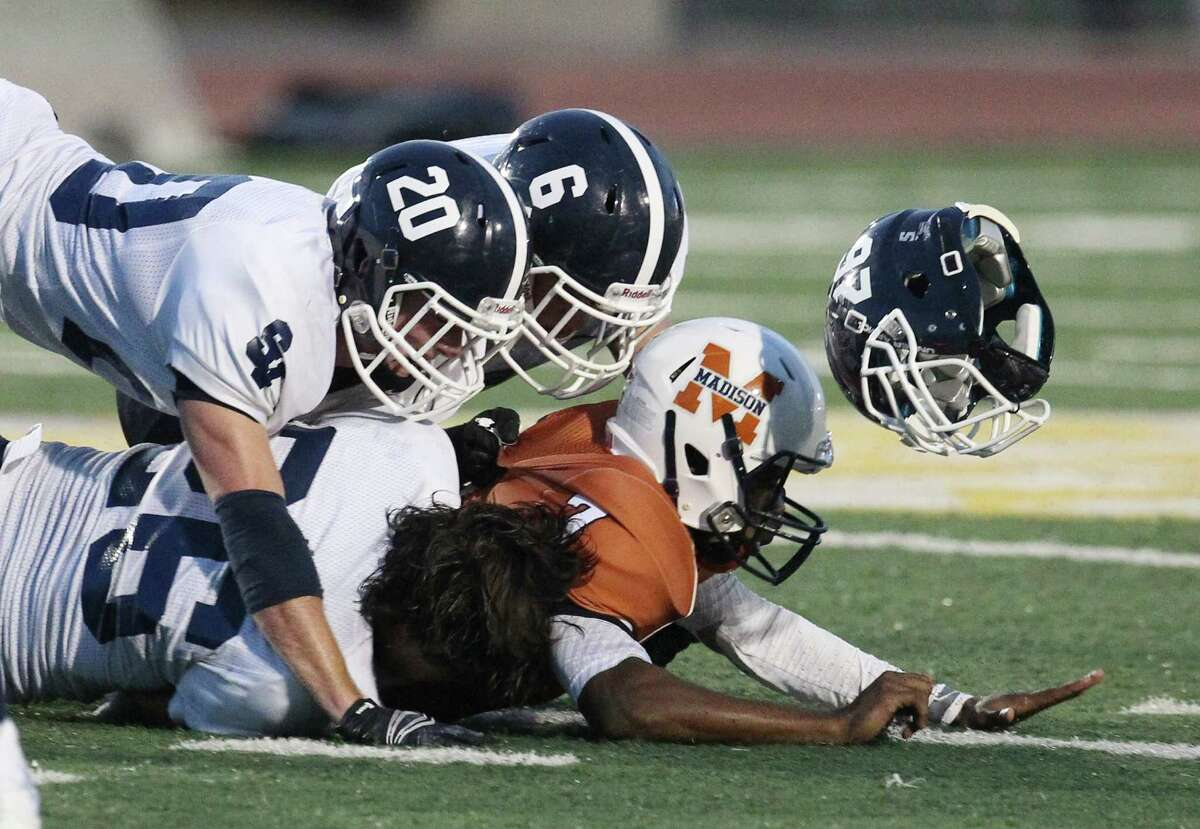 Smithson Valley's Ben Zeug (26) loses his helmet as he and teammates Brad Ingle (20) and Travis Gayre (06) go after Madison quarterback D.J. Smith at Comalander Stadium on Friday, Sept. 19, 2014.