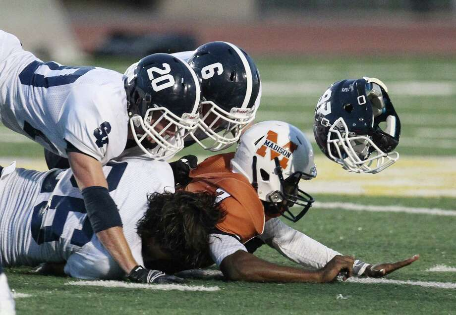 Smithson Valley's Ben Zeug (26) loses his helmet as he and teammates Brad Ingle (20) and Travis Gayre (06) go after Madison quarterback D.J. Smith at Comalander Stadium on Friday, Sept. 19, 2014. Photo: Kin Man Hui, Kin Man Hui/San Antonio Express-News / ©2014 San Antonio Express-News
