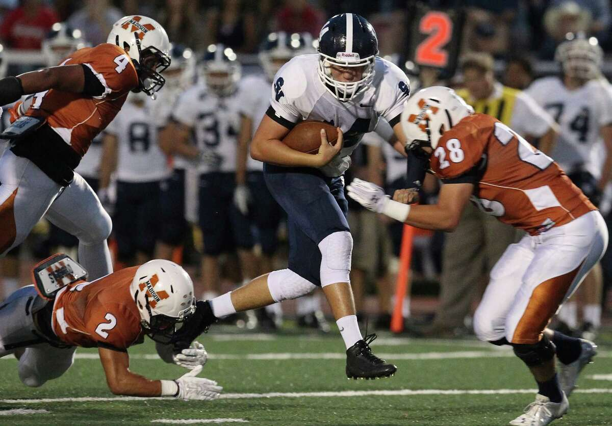 Smithson Valley quarterback Josh Adkins (14) attempts to break tackles by Madison's Jordan Gonzalez (02) and Josh Perez (28) during their game at Comalander Stadium on Friday, Sept. 19, 2014.