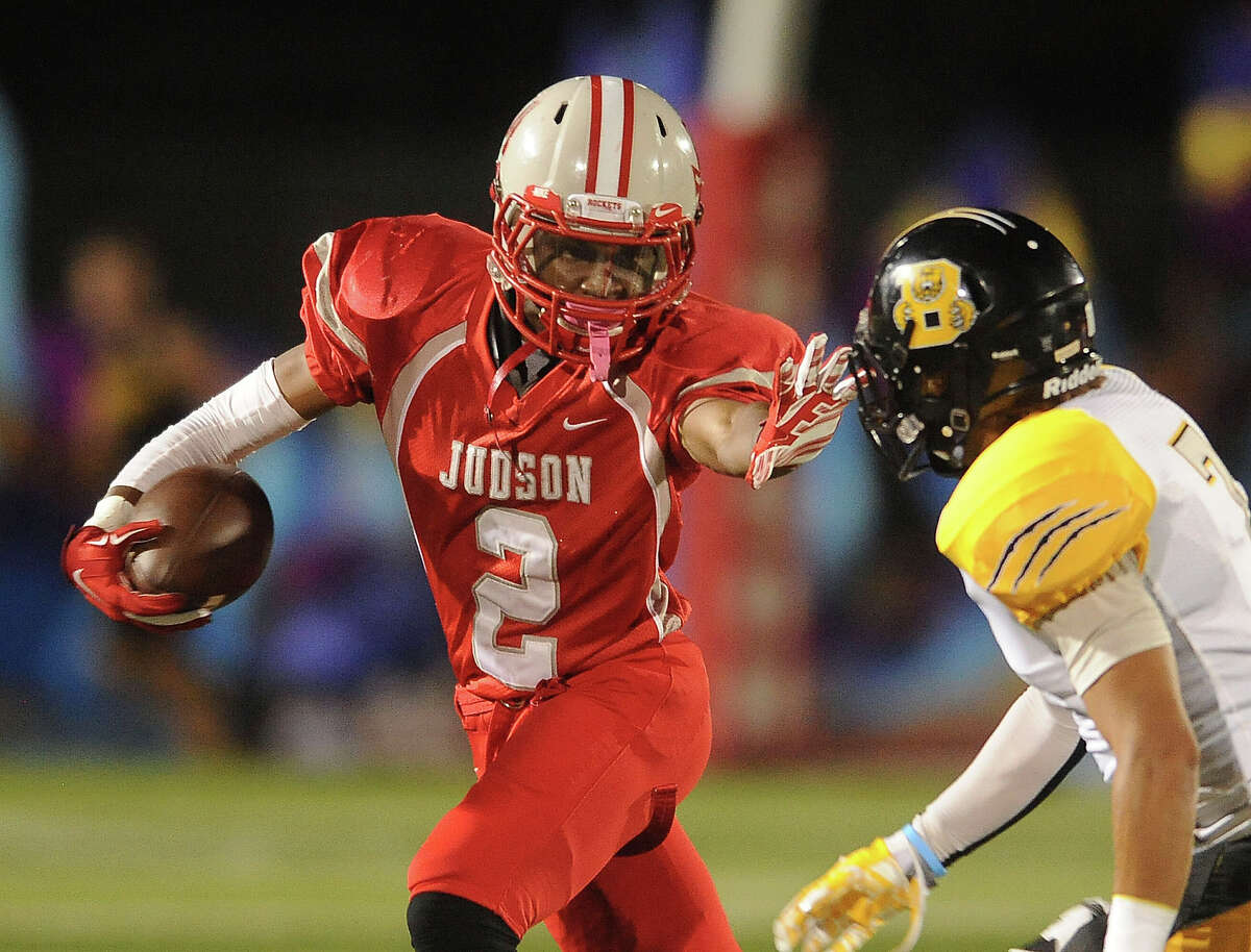 Judson runner Malik Taylor fends off Brennan's Devontre McGarity during high school football action in Converse on Friday, Sept. 19, 2014.