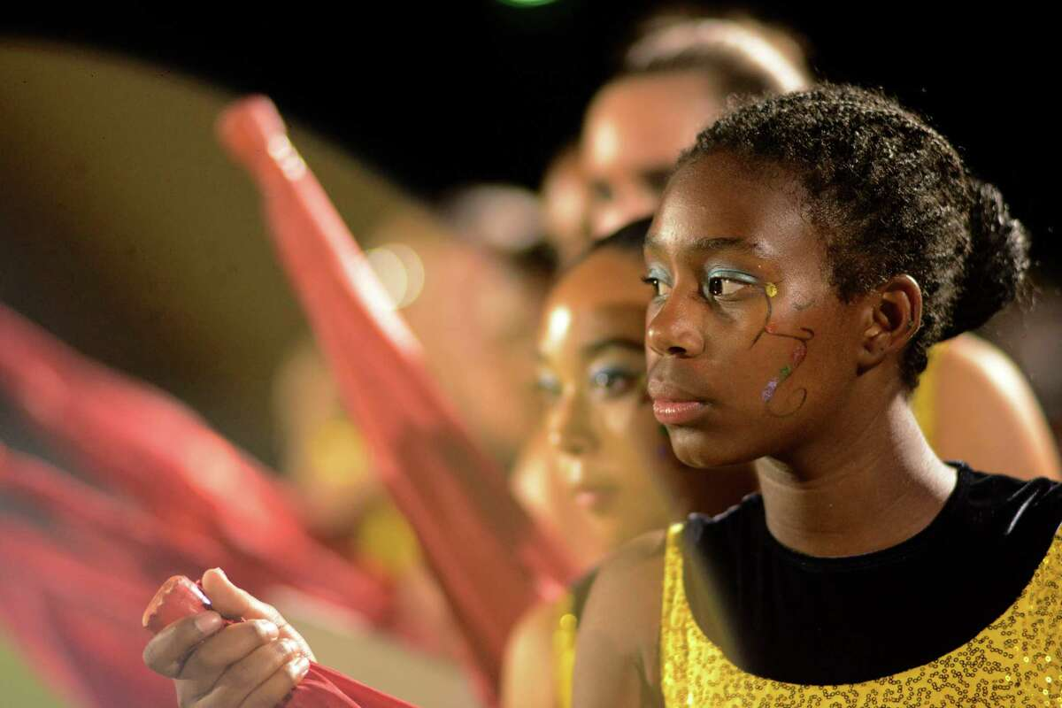 Members of the Brennan High Band flag corps prepare to perform a halftime show during high school football action in Converse on Friday, Sept. 19, 2014.