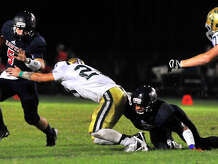 Hardin-Jefferson's Logan Thompson looks to evade a Little Cyprus-Mauriceville defender during Friday night's game in Sour Lake.  Photo taken Friday, September 19, 2014  Kim Brent/@kimbpix