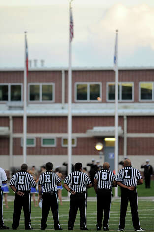 Referees prepare for the start of the game between the West Brook Bruins and the Taylor Mustangs at the Carroll Thomas Stadium Friday, Sept 19, 2014. Photo by
