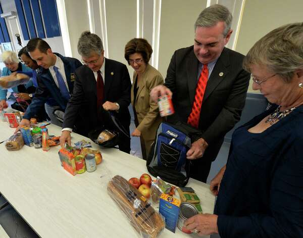 "A group of local politicians and school officials show off the food and packaging before announcement of the Weekend Backpack Program at the Pleasant Valley School Wednesday morning Sept. 17, 2014 in Schenectady, N.Y. Former Schenectady mayor Karen Johnson, right, present Schenectady mayor Gary McCarthy, second from left pack a backpack with food along with other local leaders.  The program is designed address the widespread issue of ""food insecure"" students by giving these families food that will last over the weekend while school is closed.       (Skip Dickstein/Times Union) Photo: SKIP DICKSTEIN / 00028657A"