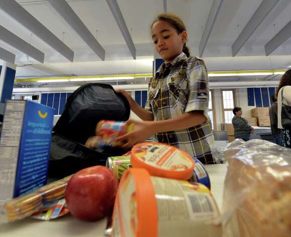 "Fourth grader Jose Castillo checks out the food that is part of the Weekend Backpack Program that was announced today at the Pleasant Valley School Wednesday morning Sept. 17, 2014 in Schenectady, N.Y.  The program is designed address the widespread issue of ""food insecure"" students by giving these families food that will last over the weekend while school is closed.       (Skip Dickstein/Times Union) Photo: SKIP DICKSTEIN / 00028657A"