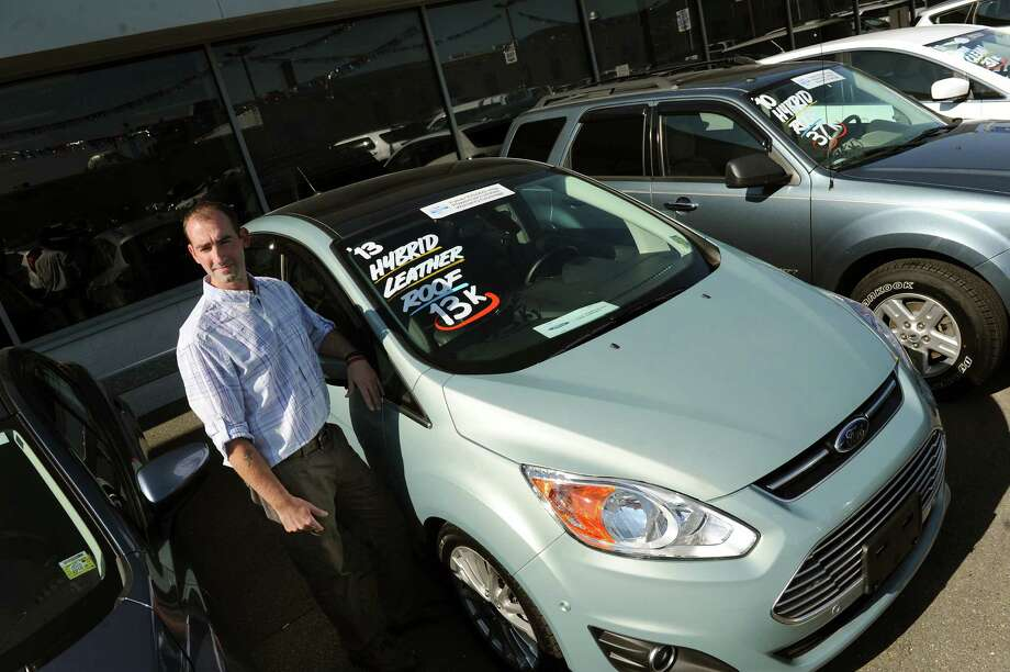 Marketing manager Brian Randio with a 2013 Ford Hybrid for sale on Friday, Sept. 19, 2014, at Orange Motor Co. in Albany, N.Y. (Cindy Schultz / Times Union) Photo: Cindy Schultz / 00028705A