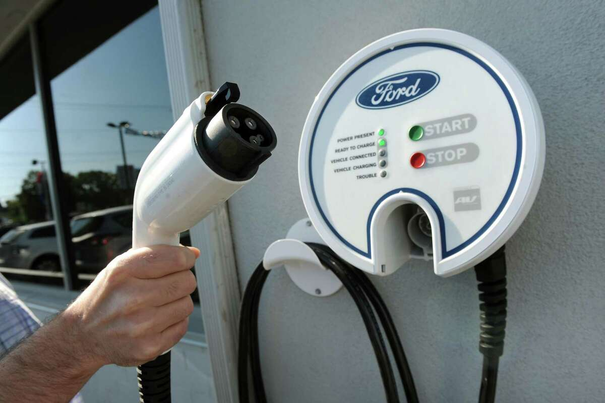 Marketing manager Brian Randio holds the hookup for an electric charger on Friday, Sept. 19, 2014, at Orange Motor Co. in Albany, N.Y. (Cindy Schultz / Times Union)