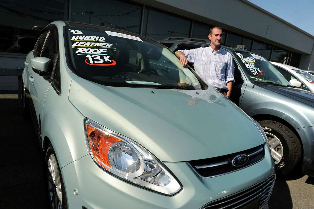 Marketing manager Brian Randio with a 2013 Ford Hybrid for sale on Friday, Sept. 19, 2014, at Orange Motor Co. in Albany, N.Y. (Cindy Schultz / Times Union)