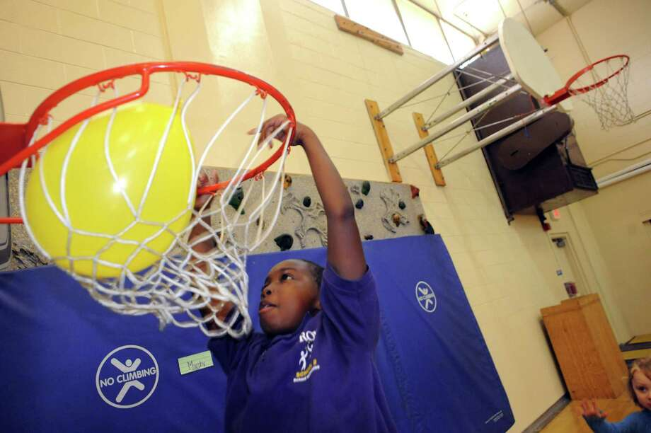 Ten-year-old Zamarion Jordon dunks a ballon through a basketball hoop during the Troy School 2 Project PROMISE gathering on Saturday Sept. 20, 2014 in Troy, N.Y. Project PROMISE is a school-wide initiative to change the overall culture and climate of our school community.  (Michael P. Farrell/Times Union) Photo: Michael P. Farrell / 00028708A