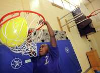Ten-year-old Zamarion Jordon, dunks a ballon through a basketball hoop during the Troy School 2 Project PROMISE gathering on Saturday Sept. 20, 2014 in Troy, N.Y. Project PROMISE is a school-wide initiative to change the overall culture and climate of our school community.  (Michael P. Farrell/Times Union)