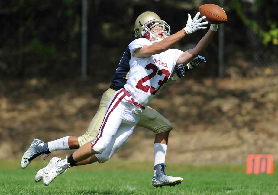 Bethel's Giovanni Luongo (23) extends his arms attempting a catch against Notre Dame Fairfield defender Andrew Chimento in Bethel's 66-36 win over Notre Dame Fairfield at Notre Dame Catholic High School in Fairfield, Conn. Saturday, Sept. 20, 2014. Photo: Tyler Sizemore / The News-Times