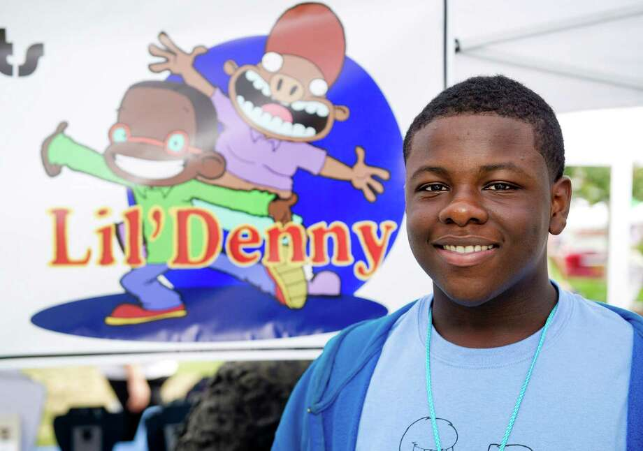 "Charles Collins, a junior at the Academy of Information Technology and Engineering, shows his comics and cartoons, which he creates as ""Chaz Daviscz,"" at a booth during Arts and Crafts on Bedford on Saturday, September 20, 2014. Photo: Lindsay Perry / Stamford Advocate"