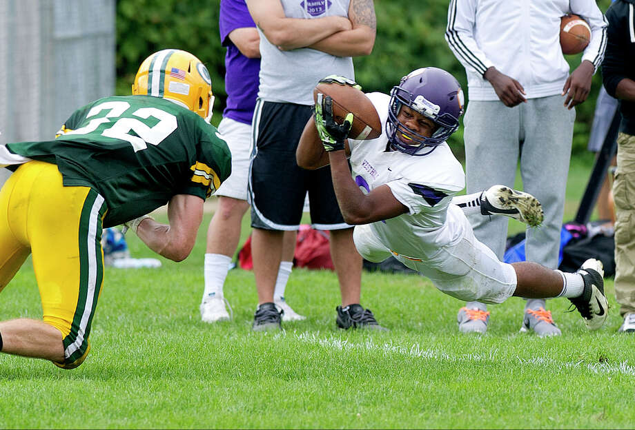 Westhill's Nasser Louis makes a diving catch during Saturday's game at Trinity Catholic High School in Stamford, Conn., on September 20, 2014. Photo: Lindsay Perry / Stamford Advocate