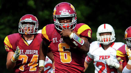 St. Joseph's Mufasha Abdul Basir breaks away to take the ball to the endzone for a touchdown, during high school football action against Fairfield Prep in Trumbull, Conn., on Saturday Sept. 20, 2014.
