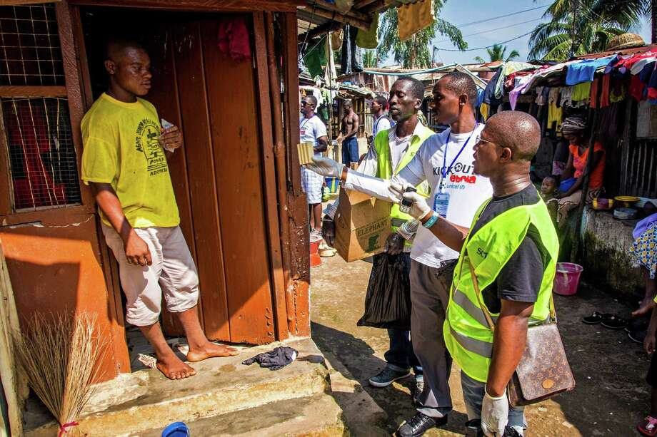 Health worker volunteers talk to a resident to distribute bars of soap and information about Ebola in Freetown, Sierra Leone, Saturday, Sept. 20, 2014. Thousands of health workers began knocking on doors across Sierra Leone on Friday in search of hidden Ebola cases with the entire West African nation locked down in their homes for three days in an unprecedented effort to combat the deadly disease. (AP Photo/Michael Duff) Photo: Michael Duff, STR / AP