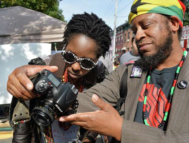 Phyllis Macharia, left, of Albany, checks out pictures taken by Robert Cooper of Troy, at this year's LarkFest street festival Saturday Sept. 20, 2014, in Albany, NY.  (John Carl D'Annibale / Times Union) Photo: John Carl D'Annibale / 00028421A