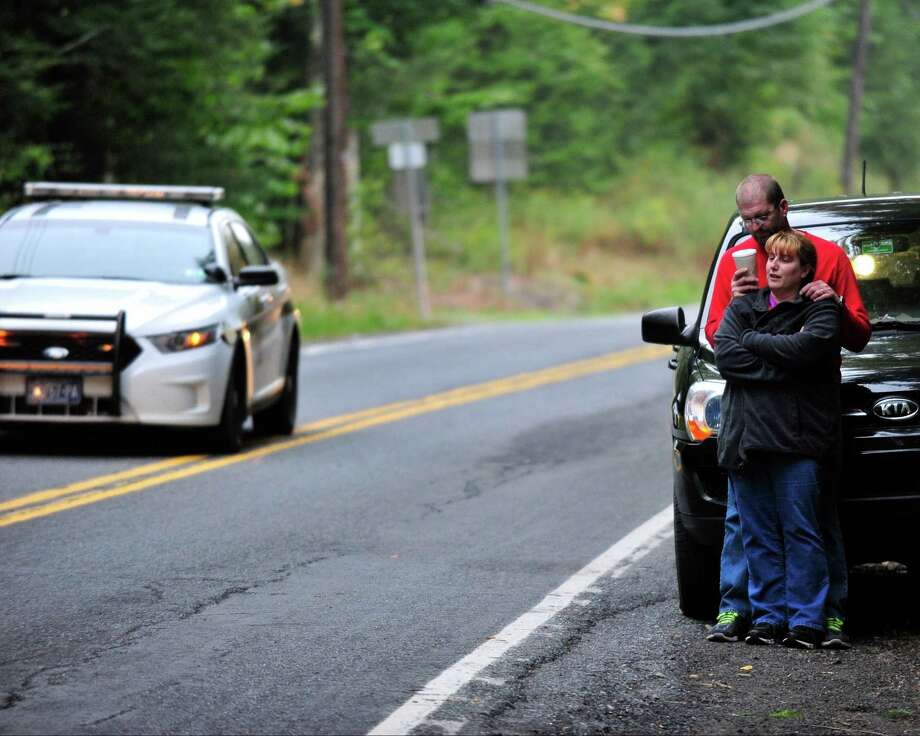 Displaced residents Jason Neff drinks coffee as he comforts his wife Jennifer Neff as police surround a neighborhood in the Pocono Mountains in search of suspect Eric Frein on Saturday, Sept. 20, 2014 in Canandensis, Pa.  Police have charged Frein with opening fire outside a state police barracks in northeastern Pennsylvania on Sept. 12. Cpl. Bryon Dickson was killed and Trooper Alex Douglass was wounded by the gunman with a high-powered rifle. (AP Photo/Chris Post) ORG XMIT: PACP101 Photo: Chris Post / FR170581 AP