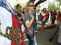 "Open Carry Texas: Women organizer Emily Grisham joins others in the Pledge of Allegiance before a rally in downtown San Antonio on Saturday, Sept. 20, 2014. The event was called ""Goddesses With Guns"" and was held to raise awareness that men aren't the the only ones interested in gun rights. With guns hung around their shoulders and flags raised the group walked several blocks toward the Alamo and back to their beginning rally site."