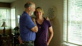 Alan Kaufman comforts his wife, Patricia, who was charged $250,000 by two plastic surgeons who sewed up an incision after her back surgery, at their home in Highland Park, N.J., Sept. 18, 2014. Medical assistants and surgical consultants, often called in without patients' knowledge, are the source of hefty fees for what some in the industry call drive-by doctoring.