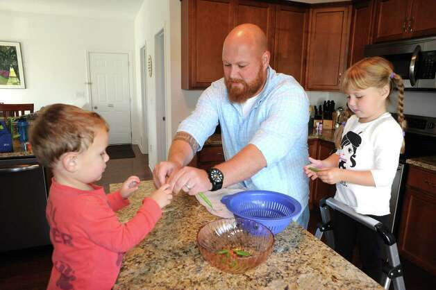 Tyler Minehan prepares diner with his two children Luke,2-years-old, and Grace, 5-years-old, on  Thursday Sept. 18, 2014 in Malta, N.Y. (Michael P. Farrell/Times Union) Photo: Michael P. Farrell / 00028685A