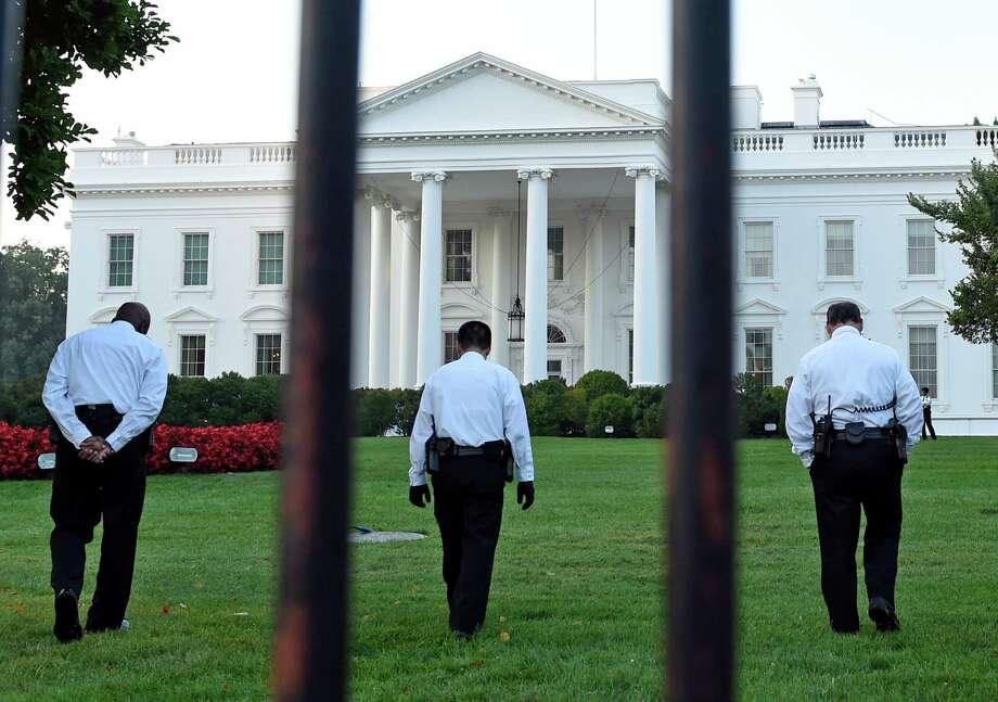 Secret Service officers inspect the lawn Saturday on the North side of the White House in Washington. The agency is coming under renewed scrutiny after a man scaled the White House fence and made it through the front door. Photo: Susan Walsh, STF / AP