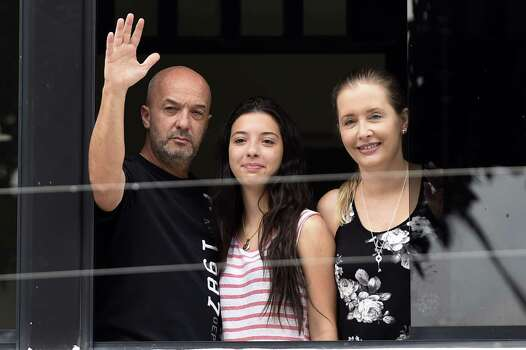 Former Caracas police commissioner Ivan Simonovis (L) waves from the window of his house next to his daughter Ivana (C) and his wife Bony Pertinez in Caracas on September 20, 2014. Simonovis, a former Venezuelan police chief jailed for his role in a failed 2002 coup against late President Hugo Chavez, has been released from prison and placed under house arrest for health reasons, his family said Saturday.  AFP  PHOTO/JUAN BARRETOJUAN BARRETO/AFP/Getty Images Photo: JUAN BARRETO, AFP/Getty Images / AFP