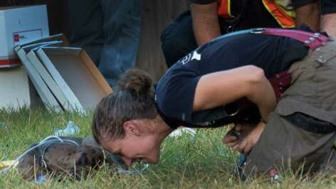 San Antonio firefighter Dawn Solinski comforts a dog that was in a house that was gutted by fire on Floral Way on Saturday, Sept. 20, 2014. The dog was hurt and treated at the scene.