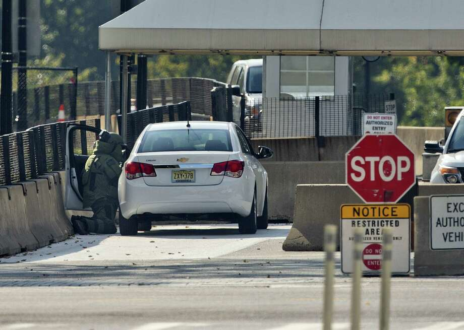 An explosive technician kneels as he searches a vehicle near the White House entrance, the second time in two days the premises have been tested. Photo: Pablo Martinez Monsivais / Associated Press / AP