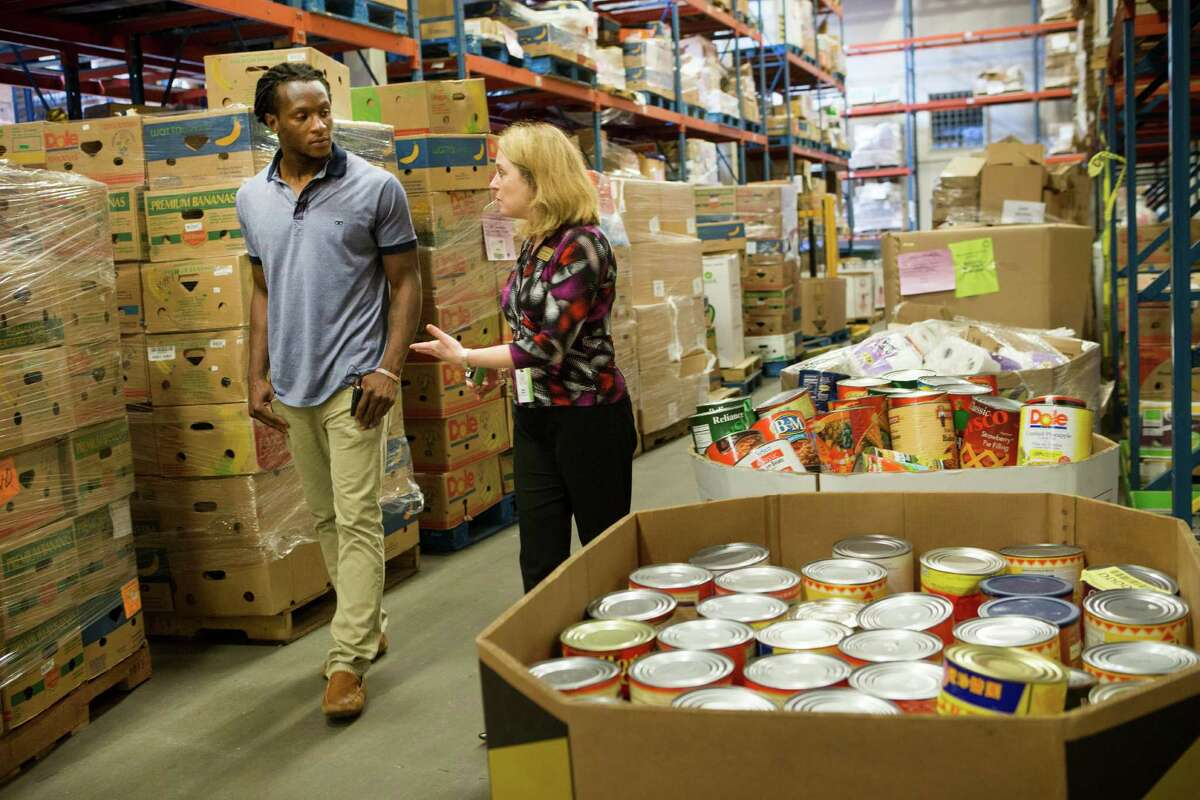 The Texans' DeAndre Hopkins, left, lends an attentive ear as he tours the Houston Food Bank with Amy Ragan, chief development officer at the food bank. Hopkins will serve as an ambassador and spokesman.