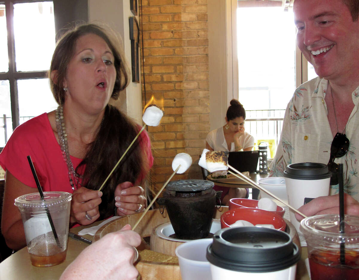 Diners make s'mores at Halcyon restaurant in Austin's warehouse district.
