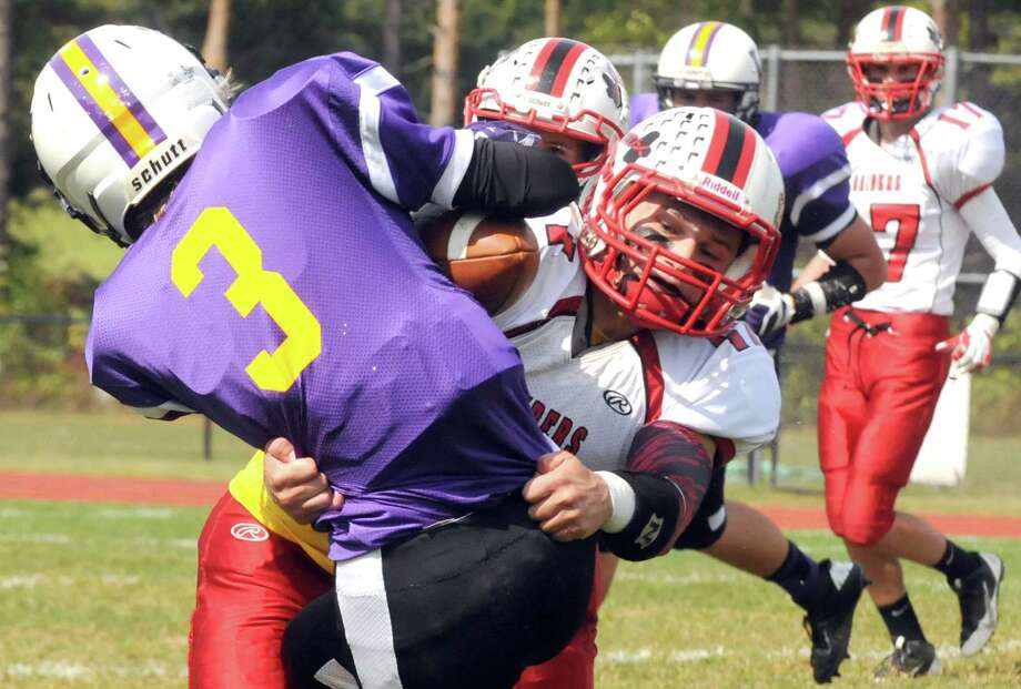 Mechanicville's Brandon Russell wraps up Voorheesville's George Bernhard after a catch during their boy's high school football game on Saturday Sept. 20, 2014 in Voorheesville, N.Y.  (Michael P. Farrell/Times Union) Photo: Michael P. Farrell / 00028673A