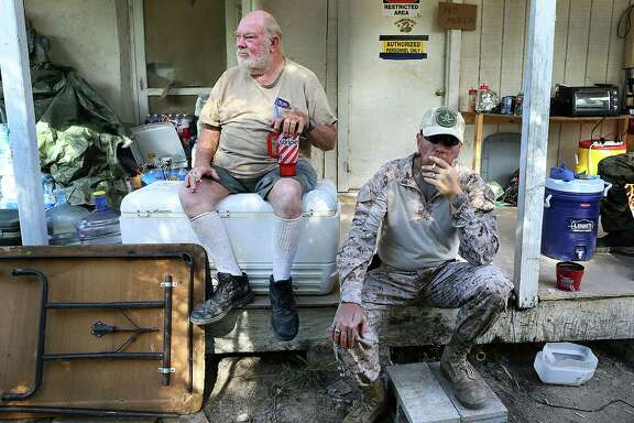 "Kevin ""KC"" Massey, right, takes a drag on a cigarette as he sits with Rusty Monsees Jr., who asked the militia group, called Camp Lonestar, to set up on his property along the Rio Grande in Brownsville."