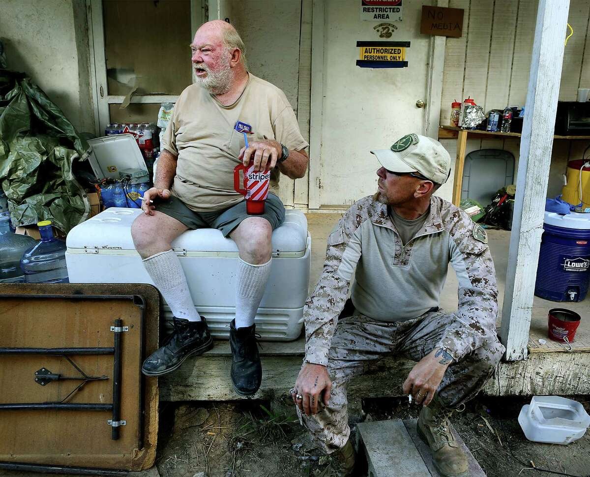 KC Massey, right, listens to land owner Rusty Monsees Jr. as they sit on the porch of an old house on Monsees's property. Monsees asked the militia group called Camp Lone Star, to set up camp on his property along the Rio Grande River in Brownsville, TX. Wednesday, September 10, 2014
