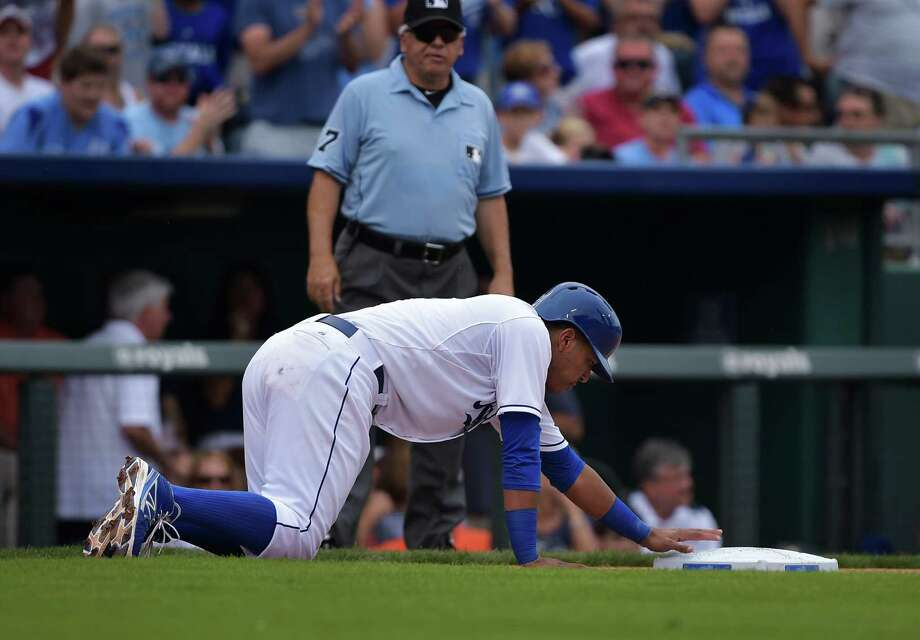 Kansas City Royals catcher Salvador Perez (13) crawls back to third base after over running it during the sixth inning of their baseball game against the Detroit Tigers, Saturday, Sept. 20, 2014, in Kansas City, Mo. Later in the inning he'd be called out on a base-running error.  (AP Photo/Reed Hoffmann) ORG XMIT: MORH127 Photo: Reed Hoffmann / FR48783 AP