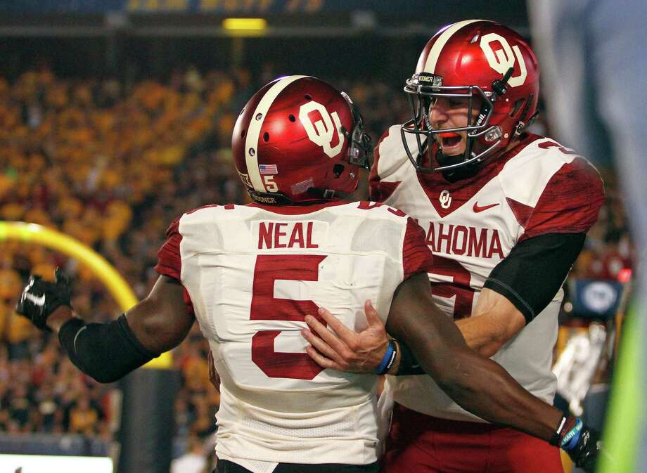 Oklahoma quarterback Trevor Knight, right, joins Durron Neal in celebrating their 4-yard hookup for a second-quarter touchdown against West Virginia. Photo: Justin K. Aller, Stringer / 2014 Getty Images